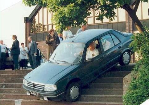 Eine Frau fährt mit einem Auto eine Treppe runter.