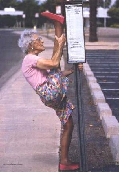 Eine Oma dehnt sich und macht einen Spagat an einer Bushaltestelle.