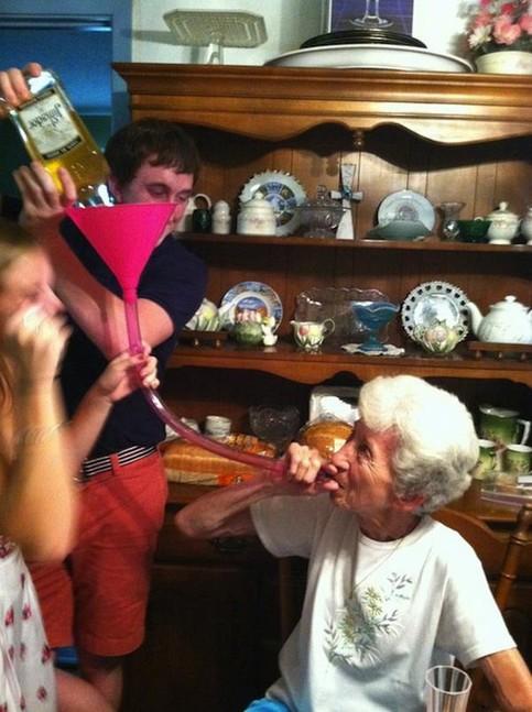 Eine alte Frau hat einen Schlauch im Mund, am anderen Ende des Schlauchs ist ein Trichter. Dort kippen Jugendliche Alkohol hinein, eine sogenannte Bierbong.
