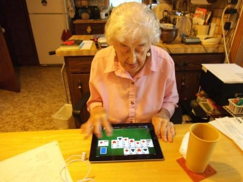 Eine Oma spielt an einem iPad-Tablet ein Kartenspiel, sie sieht dabei sehr konzentriert aus.