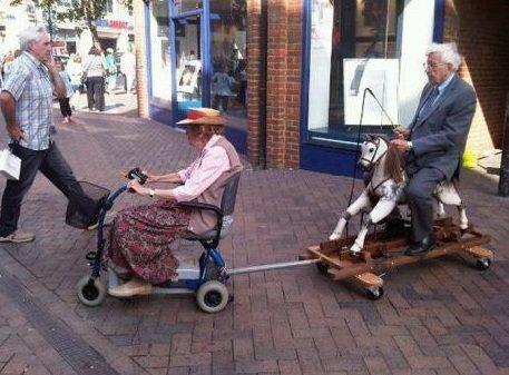 Eine alte Frau sitzt auf einem Elektrorollstuhl und zieht damit einen alten Mann der auf einem Schaukelpferd sitzt.