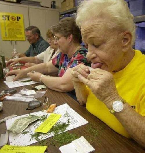 Ältere Frauen und Männer sitzen an einem Tisch und drehen Zigaretten.