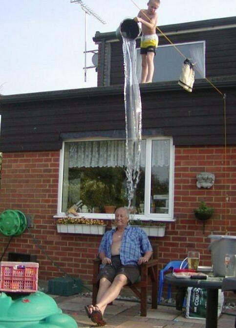 Ein Junge kippt von einem Dach einen Eimer Wasser auf einen Opa.