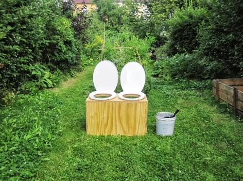 In einem Garten sind zwei nebeneinander stehende Klos unter freiem Himmel aufgestellt.