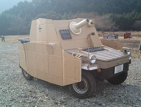 Ein Auto mit einer Abdeckung aus Pappe, sieht aus wie ein Panzer.