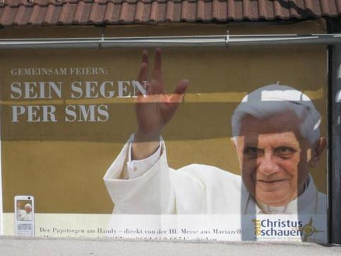 Der Papst bietet auf einem Plakat seinen Segen per SMS an.