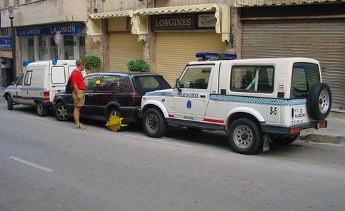 Ein Auto ist mit einer Parkkralle gestoppt und ist von zwei Polizeiautos eingeparkt.