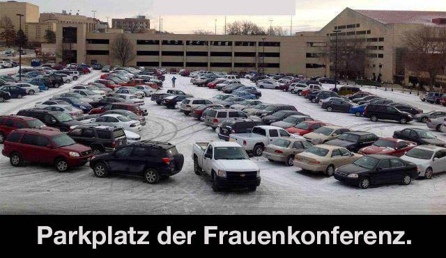 """Auf einem Parkplatz stehen Autos chaotisch durcheinander. Darunter steht der Text: """"Parkplatz der Frauenkonferenz""""."""