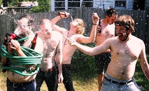 Fünf junge Männer feiern wild mit herumspritzendem Bier und einem Gartenschlauch.