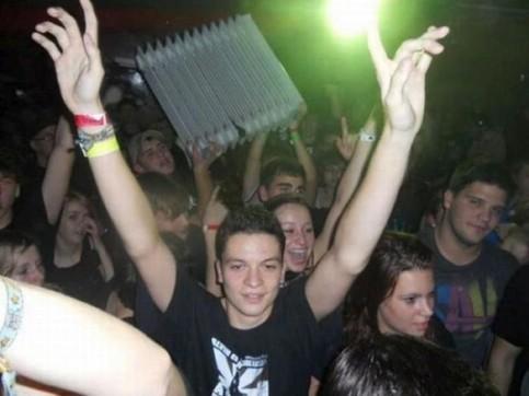 Auf einer Party hält ein Jugendlicher eine Heizung in die Höhe.