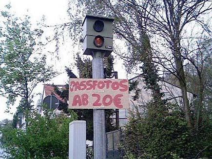 """Eine Radarfalle ist mit einen Schild """"Passfotos ab 20 Euro"""" behängt."""