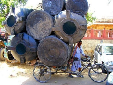 Ein Mann hat auf einem Fahrrad riesige Metallbehälter geladen.