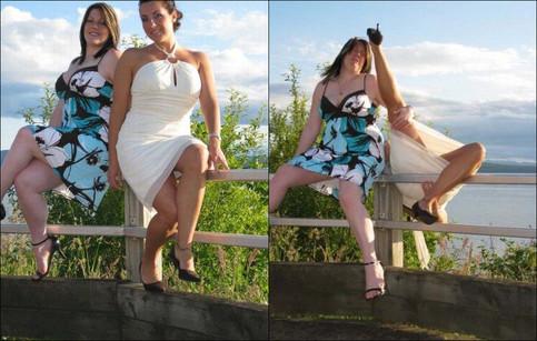 Zwei Frauen sitzen auf einem Geländer und posieren für ein Foto. Eine der beiden fällt nach hinten um, die andere versucht sie zu halten.