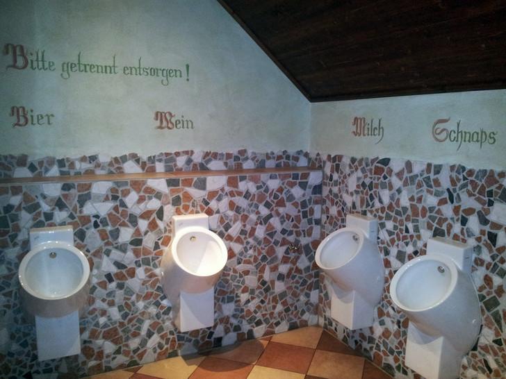 """Auf einem WC steht an der Wand """"Bitte getrennt entsorgen!"""". Über den WC-Pissoirs steht """"Bier, Wein, Milch, Schnaps""""."""