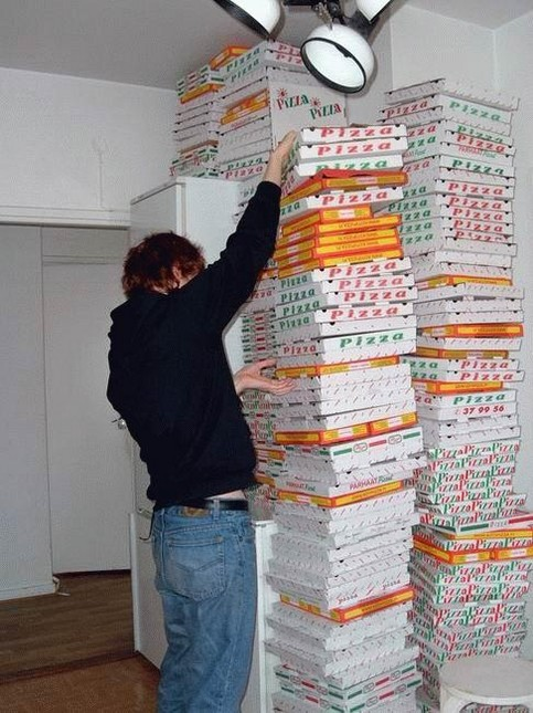 Ein Mann mit einem Riesen-Stapel von Pizza-Kartons.