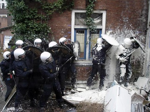 Polizisten werden mit Farbe begossen.