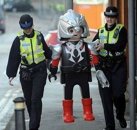 Polizisten führen ein großes Playmobil-Männchen ab.