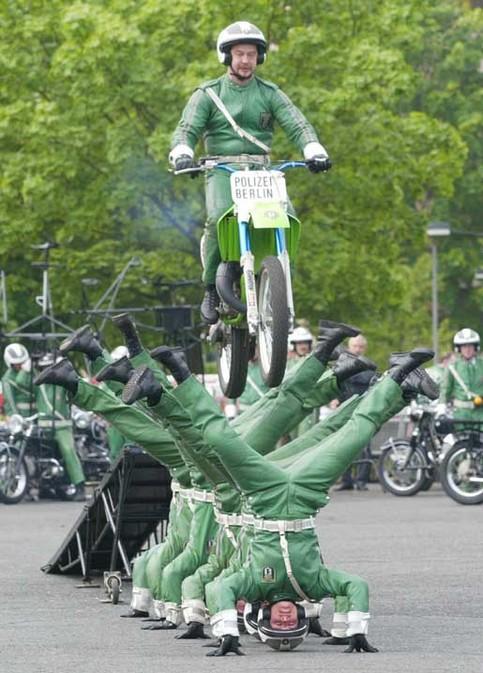 Ein Polizist springt mit einem Motorrad über andere Polizisten.