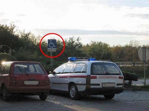 Ein Polizei-Auto parkt auf einem Behinderten-Parkplatz.