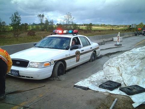 Ein Polizeiwagen ist in frischen Beton gefahren und stecken geblieben.