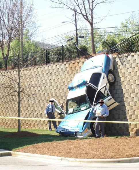 Ein Polizeiauto ist eine mehrere Meter hohe Mauer hinunter gestürzt.