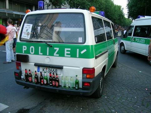 Auf der Stoßstange eines Polizeibuses sind Bierflaschen abgestellt.