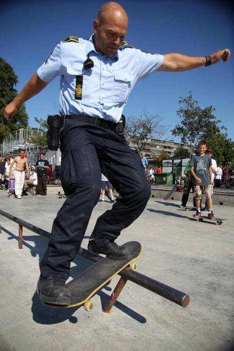 Ein Polizist grindet mit einem Skateboard über eine Rail. Um ihn herum stehen Jugendliche und freuen sich über den coolen Polizisten.