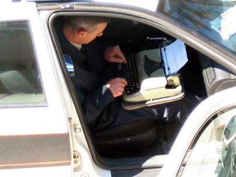 Ein Polizist sitzt einem Polizeiauto und schreibt auf einer Schreibmaschine.