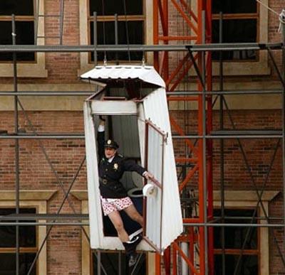 Ein Polizist hängt an einem Klo, das von einem Kran in die Höhe gezogen wird.