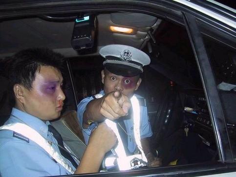 Zwei asiatische Polizisten mit blauen Augen zeigen mit dem Finger auf die Kamera.