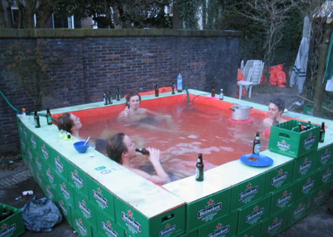 Jungs sitzen in einem Pool, der aus Bierkästen gebaut wurde.