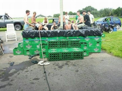 Junge Leute haben aus vielen leeren Bierkisten und einer Teichfolie einen Pool gebaut.