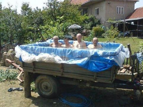 Vier Männer sitzen in einem Pool, den sie aus einem Traktoranhänger und Planen gebaut haben.