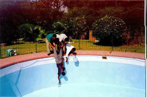 Ein Pool Schwimmbad wird von Männern gereinigt, die einen anderen Mann an den Beinen runter lassen.