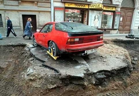 Ein Porsche mit einer Parkkralle, um ihn herum ist die Strasse zerstört.