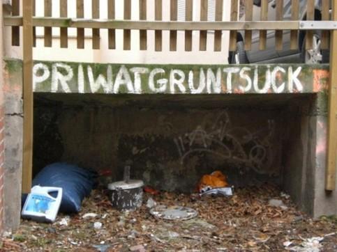"""Über einer Schlafgelegenheit für Obdachlose steht geschrieben: """"Priwatgruntsück""""."""