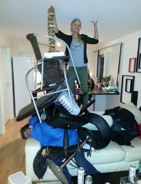 Auf einem schlafenden, bemalten und offensichtlich besoffenen Mann hat eine Frau eine Pyramide aus Gegenständen wie Stühlen genau. Die Pyramide reicht bis zur Decke, sie steht oben und freut sich.