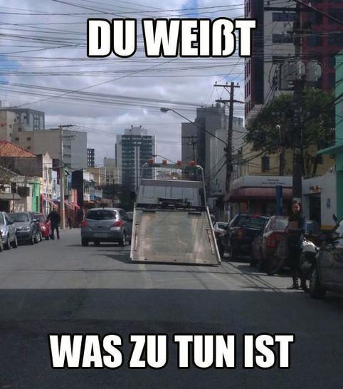 """Ein Autotransporter steht mit heruntergelassener Rampe auf der Straße. Dazu steht der Text """"Du weißt was zu tun ist""""."""