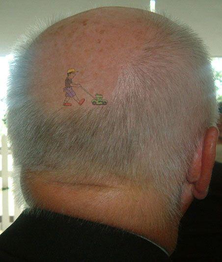 Ein Mann hat auf seinem Hinterkopf am Glatzenansatz einen Rasenmäher eintätowiert.
