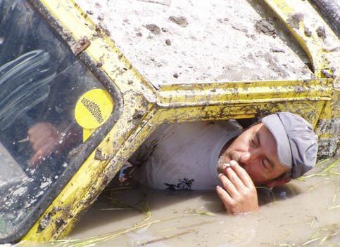 Ein lässiger Fahrer in einem Geländewagen, der rauchend aus dem Fenster schaut, obwohl sein Wagen tief im Schlamm steckt.