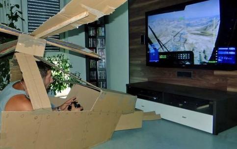 Ein Mann spielt auf einer Spielkonsole einen Hubschrauber-Simulator. Dabei sitzt er in einem selbstgebauten Hubschrauber aus Pappe.