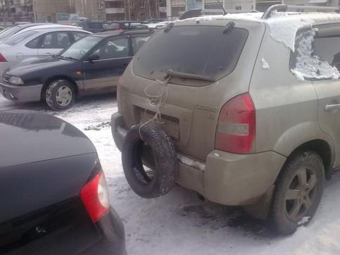 An der Heckklappe eines Autos ist ein Autoreifen befestigt, als zusätzliche Stoßstange.