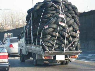 Ein LKW ist mit einem riesigen Haufen Reifen beladen.