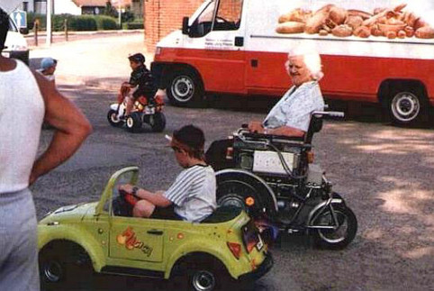 Ein Junge überholt mit seinem Spielzeug-Auto eine Oma im Elektro-Rollstuhl