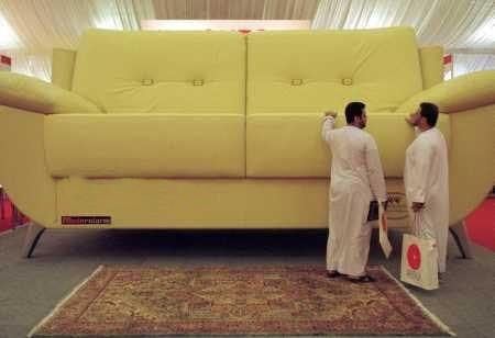 Ein Möbelhaus, in dem zwei Männer vor einem riesigen Sofa stehen.