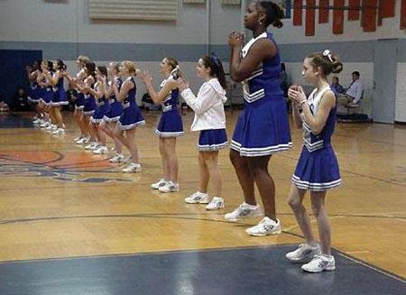 Eine Reihe von Cheerleadern, wobei eine viel größer ist als die anderen sind.