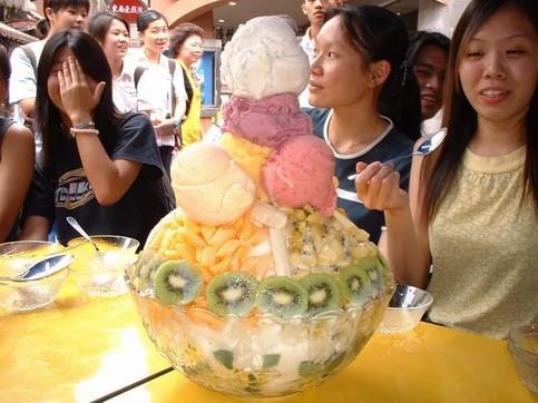 Lauter Asiaten sitzen um ein riesiges Glas mit Eis herum.