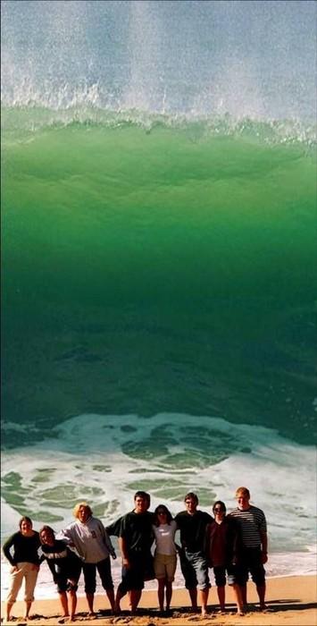 Eine Gruppe Jugendlicher lässt sich an einem Strand fotografieren, während von hinten eine Riesenwelle auf sie zu kommt.