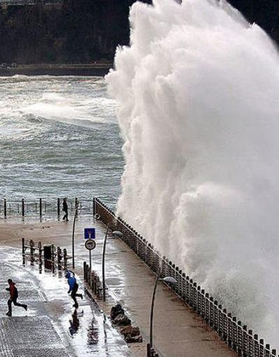 Eine meterhohe Welle an einem Kai.