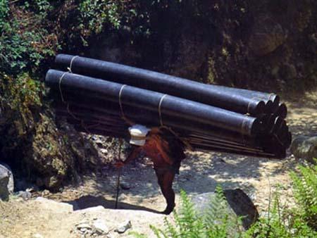 Ein Mann schleppt Rohre auf dem Rücken einen Berg hinauf.